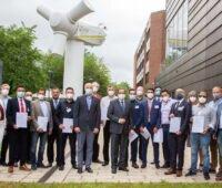 Ein Gruppe Absolventen (mit Maske) im Hintergrund das aufgeständerte Generatorhaus einer Windkraftanlage