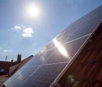 Eine Solaranlage auf Schrägdach im Gegenlicht der Sonne am Himmel.