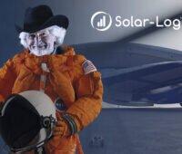 Foto: weißhaariger Mann mit schwarzem Hut im orangefarbenen Raumanzug und Raumfahrhelm in der Hand und rechts oben Solar-Log: mit Solar-Log ins Weltall