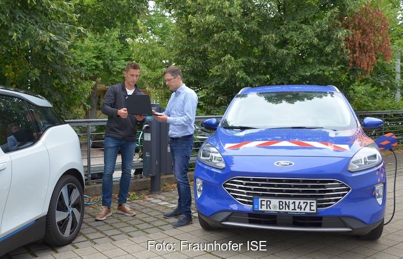 Zwei Männer mit Laptop stehen zwischen zwei Autos - Praxistest für Stromnetz und Ladesystem.