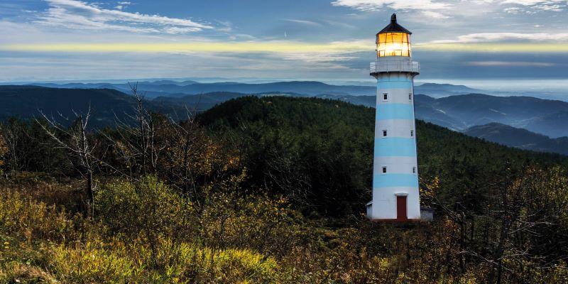 Ein Leuchtturm steht in einem Mittelgebirge.