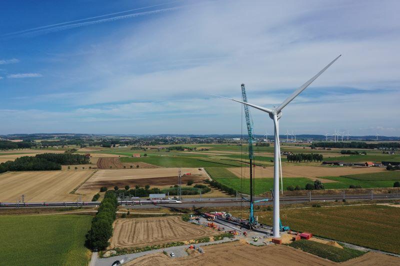 Eine Windkraftanlage während der Errichtung in einer flachen ländlichen Region mit Windpark am Horizont.
