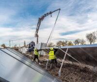 Arbeiter in gelben Westen installieren Solarkollektoren.
