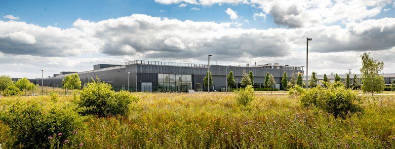 Ein modernes Industriegebäude umgeben von bunten Blumen und Büschen.