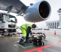 Zu sehen ist ein Flugzeugtriebwerk und ein Arbeiter beim Betanken eines Flugzeugs. Ein CO₂-freier Flugverkehr erfordert synthetische Treibstoffe.