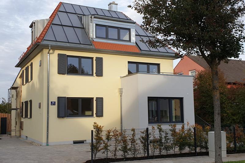 Ein Mehrfamilienhaus mit einer Solarthermieanlage auf dem Spitzdach.