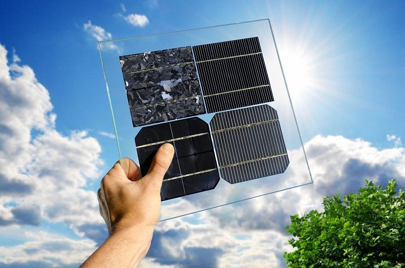 Zu sehen ist eine Hand, die verschiedene Solarzellen in die Sonne hält. Solarzellen aus ferroelektrischen Kristallen könnten eine Alternative zur Silizium-Solarzelle sein, die heutzutage in den meisten Photovoltaik-Modulen zum Einsatz kommt.