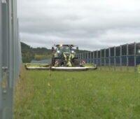 Ein Mähdrescher bei der Arbeit zwischen vertikalen Solarmodulen.