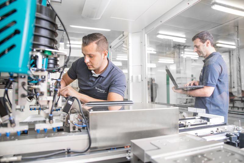 Arbeiter bedienen moderne Maschinen für elektrotechnische Anwendungen