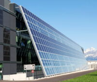 Zu sehen ist eine Solarfassade der Firmenzentrale von Meyer Burger, im HIntergrund die Alpen.