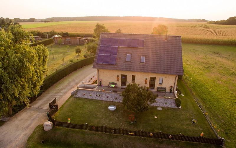 Ein freistehendes Einfamilienhaus auf dem Lande beim Sonnenuntergang, von oben fotografiert mit Blick auf Spitzdach mit PV-Anlage.