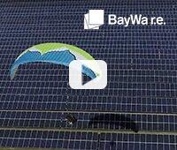 Bild mit Paraglider, der auf einer PV-Freiflächen Anlage landet