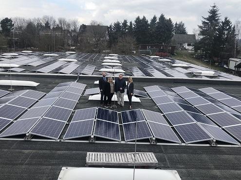 Foto von einer PV-Anlage auf einem Flachdach. In der Mitte stehen 2 Männer und 2 Frauen auf dem Dach.