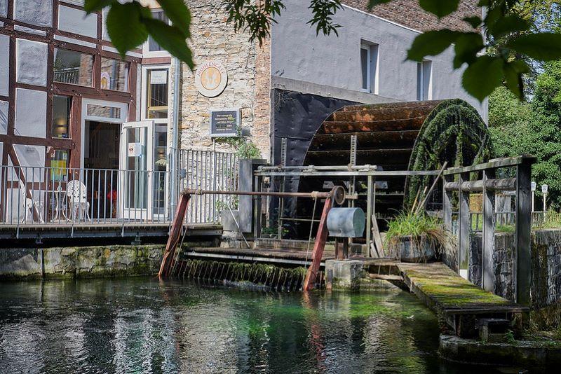 Ein altes Mühlengebäude mit historischem Wasserrad.