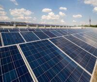 Eine Solaranlage auf einem Flachdach. Im HIntergrund der Münchener Olympiaturm.