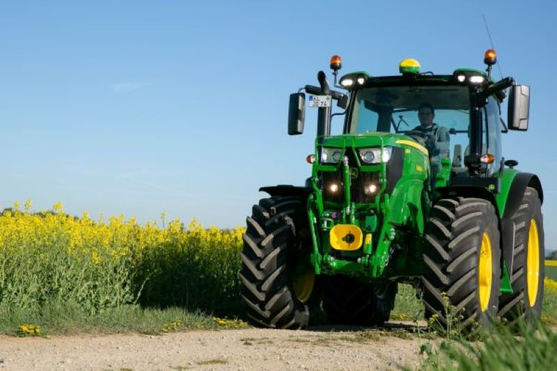 Ein Traktor fährt an einem Rapsfeld entlang.
