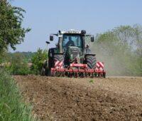Zu sehen ist ein Traktor bei der Aussaat der Blühwiesen als Substrat für Biogas-Anlagen.