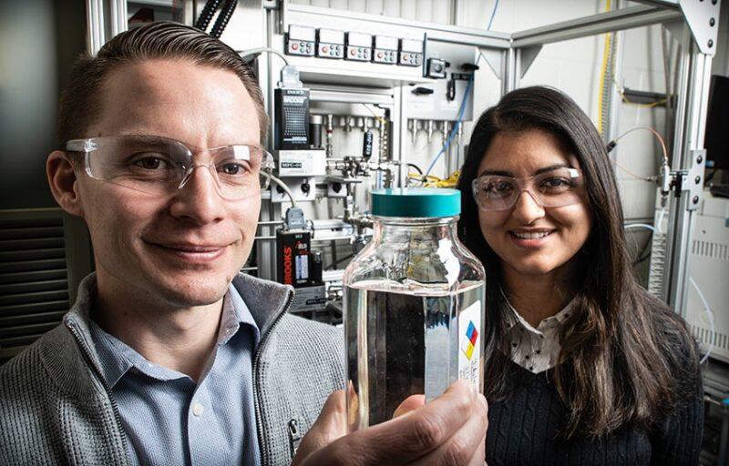 Die Forscher Derek Vardon und Nabila Huq zeigen eine Behälter mit dem Biokraftstoff.