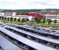 Zu sehen ist ein mit PV-Modulen überdachter Firmenparkplatz mit hunderten von Parkplätzen. Die Photovoltaik-Pflicht für neue Parkplätze in NRW soll ab 35 Stellplätzen greifen.