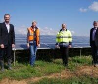 4 Personen vor einem Solarkraftwerk bei blauem Himmel.