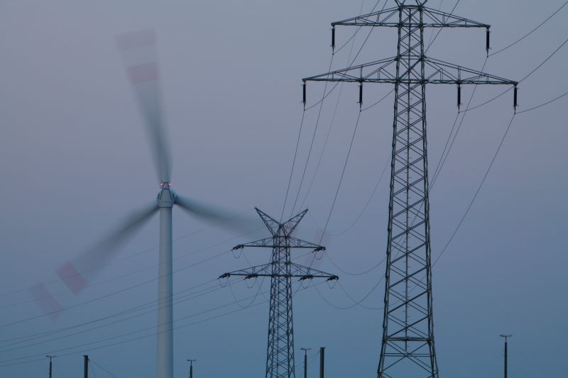 Rotierende Windmühle neben Strommasten