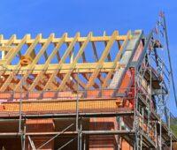 Zu sehen ist ein Dachstuhl in Arbeit. Erneuerbare Energien zur Heizung sind gefragt.
