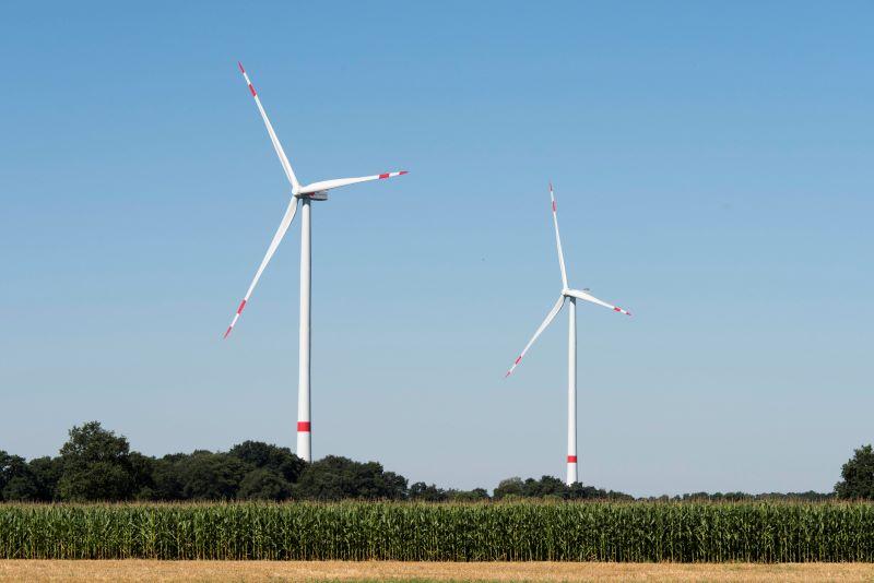 Zwei Windenergieanlagen in einer ländlichen Umgebung.