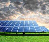Ein Freiflächensolarpark unter bewegtem Himmel und auf grüner Wiese.
