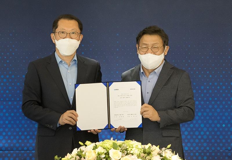 Zu sehen sind Hee Cheul, CEO von Q Cells, und JaeSeung Lee, President und Head of Digital Appliances Business bei Samsung Electronics unterzeichnen die Vereinbarung für die Zusammenarbeit beim Nullenergiehaus.