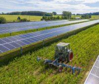 Aufgeständerte Solarmodulreihen beschatten eine Agrarfläche, dazwischen fährt ein Traktor.