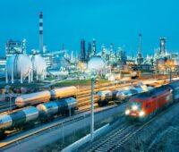 Eine beleuchtete Raffinerie am Abend mit im Vordergrund vorbeifahrenden Zügen.