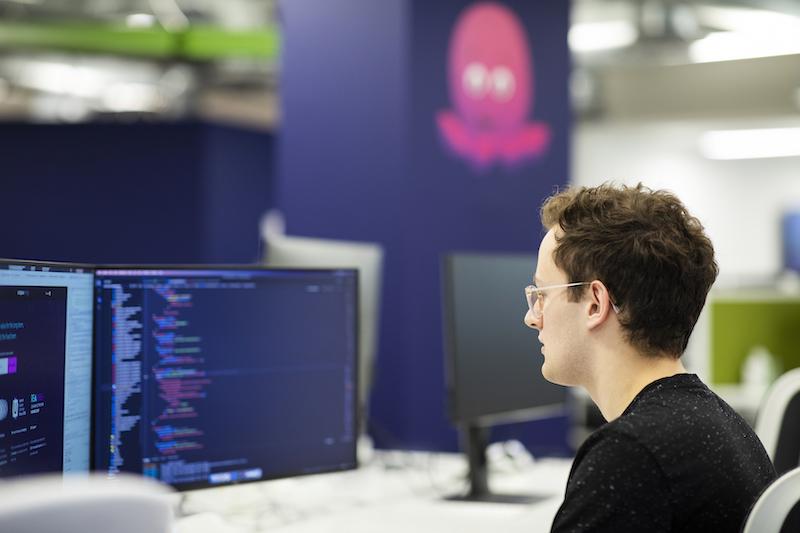 Programmierer sitzt vor Bildschirm - mit KI will Octopus Energy die Kosten für Ökostrom senken.