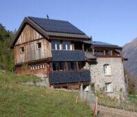 Zu sehen ist eine Berghütte mit PV auf dem Dach und an der Fassade. Die Einspeisetarifförderung für Photovoltaik-Dachanlagen in Österreich ist stark nachgefragt.