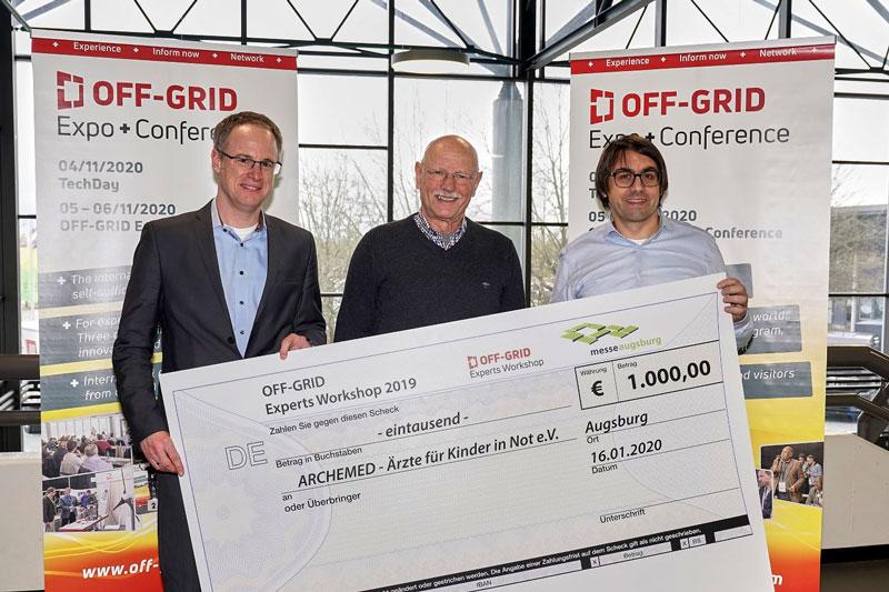 Drei Männer mit symbolischem Scheck über 1000 Euro