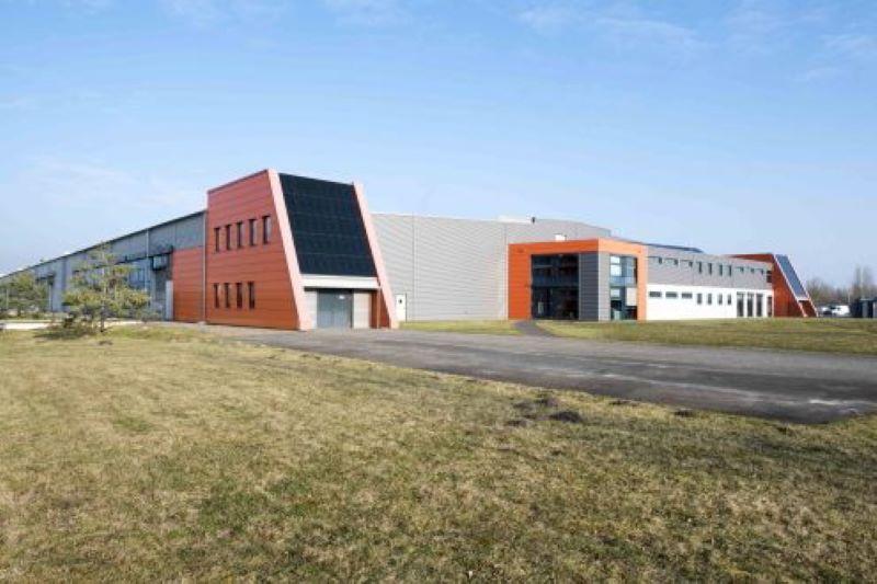 Ein flaches Industriegebäude auf grüner Wiese.