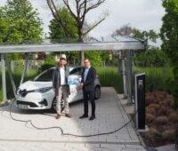 Zwei Männer mit Elektroauto präsentieren eine Broschüre.