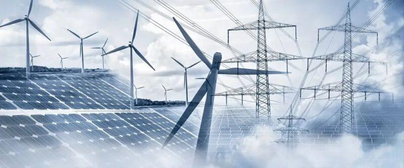 Zu sehen ist ein symbolisches Bild mit Strommasten, PV-Anlagen und Windkraftanlagen, die für wasserstoffbasierte Brennstoffe nötig sind.