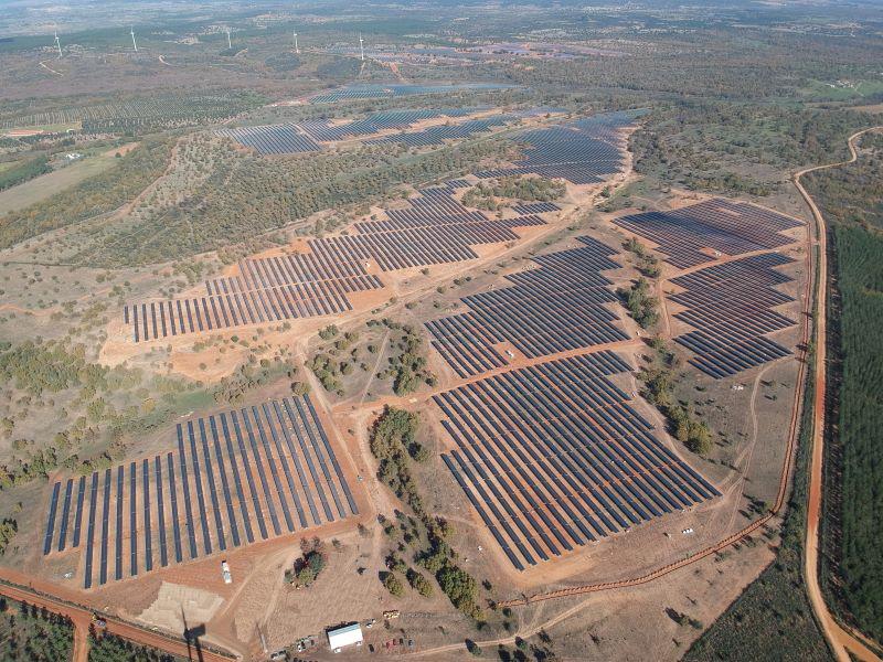 Luftaufnahme eines PV-Parks in Spanien mit Windenergie im Hintergrund