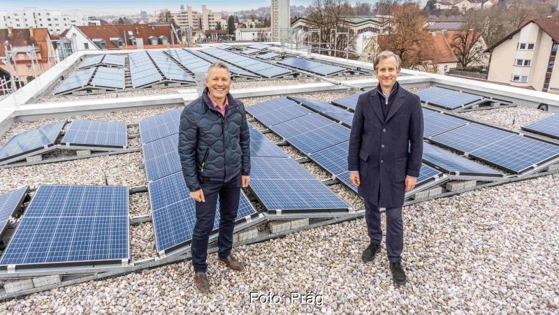Zwei Männer lachend auf einem Flachdach mit Solaranlagen.
