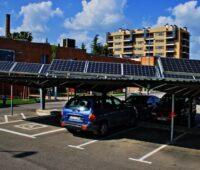Autos auf einem mit PV-Modulen überdachten Parkplatz.