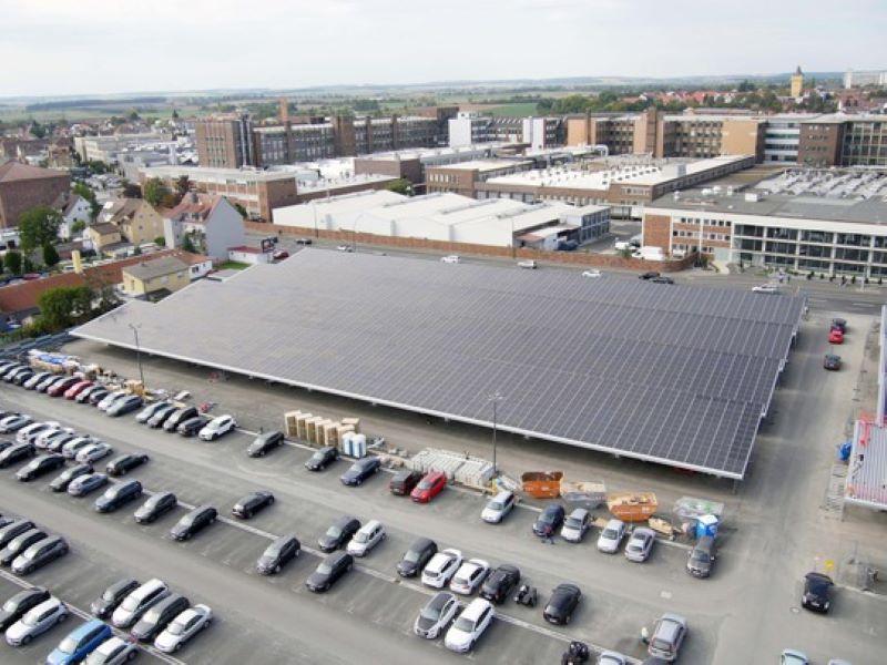 Ein mit einer PV-Anlage teils überdachter Parkplatz eines Unternehmens.