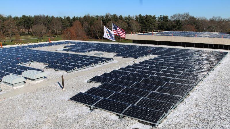 Ein Firmendach ist mit Photovoltaik bestückt. Außerdem weht dort eine kleine US-Flagge.