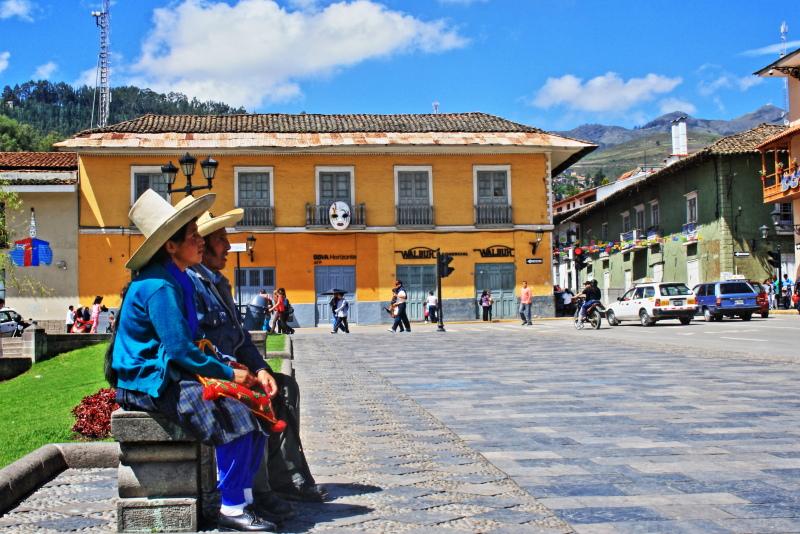 Auf dem von den Spaniern einst gebauten Hauptplatz der peruanischen stadt Cajamarca sitzt ein indigenes Paar in traditioneller Ttacht. Im Hintergrund die Anden.