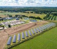 Luftbild einer Kläranlage mit Klärbecken und einer Reihe von Solarmodulen.