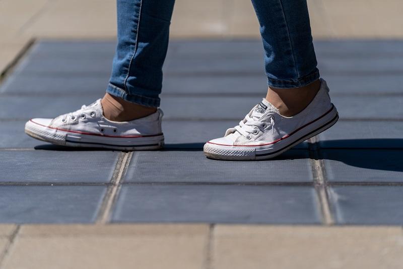 Im Bild ein begehbares Solarpflaster aus Photovoltaik-Modulen, auf dem ein Mensch spaziert, von dem sie Schuhe zu sehen sind.