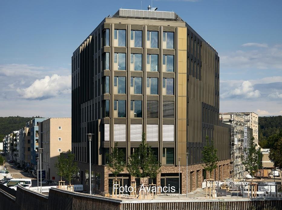Zu sehen ist das Gebäude Westspitze, bei dem man die bronzefarbenen Solarfassadenmodule von Avancis verbaut hat.