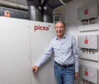 Ein lachender Mann hat sich in seinem Keller vor seinen Stromspeicher gestellt.