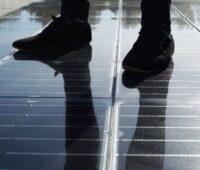 Eine solare Gehwegplatte mit einem paar beschuhter Füße.