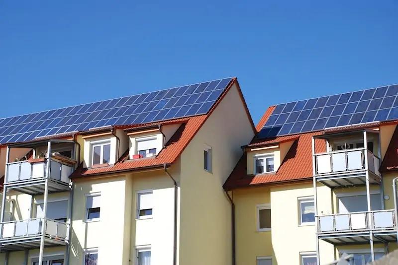 Zu sehen ist ein Mehrfamilienhaus mit Photovoltaik-Anlage. Die neue BEG-Förderung verbessert die Bedingungen für Mieterstrom.