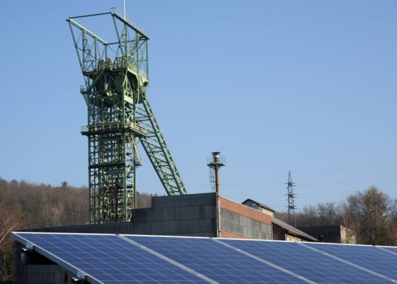 Vor einem Förderturm für Kohle ist ein Solardach installiert